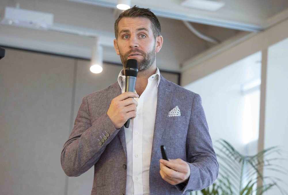 Mr. Michael Glancy, Director of Markets for JLL, speaking on trends and the development of collaborative space in Kowloon East, at the WeWork Two Harbour Square location.