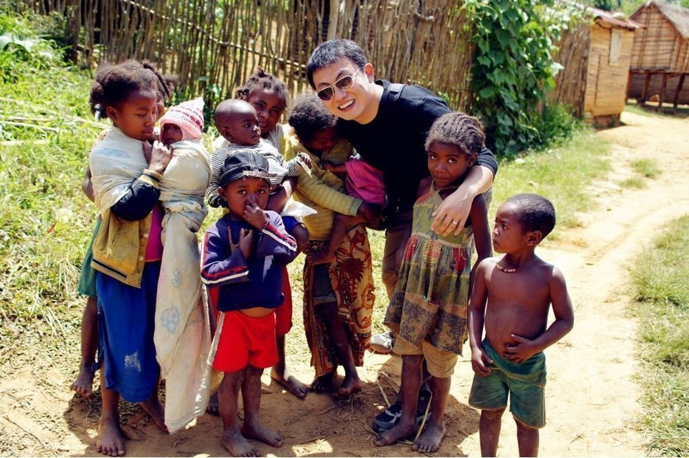 Troy befriending locals on one of his trips to Madagascar (Source: Mileslife)